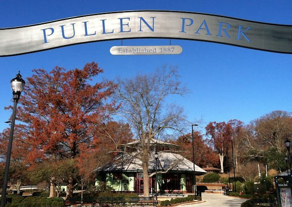 A photo of the entrance to Pullen Park, which includes a lovely silver sign which reads 'Pullen Park, established in 1887'; Pullen Park is immediately west of downtown Raleigh, North Carolina. Located on Raleigh's iconic Hillsborough Street and adjacent to the main campus of North Carolina State University, Pullen Park, founded in 1887, is the oldest public park in North Carolina