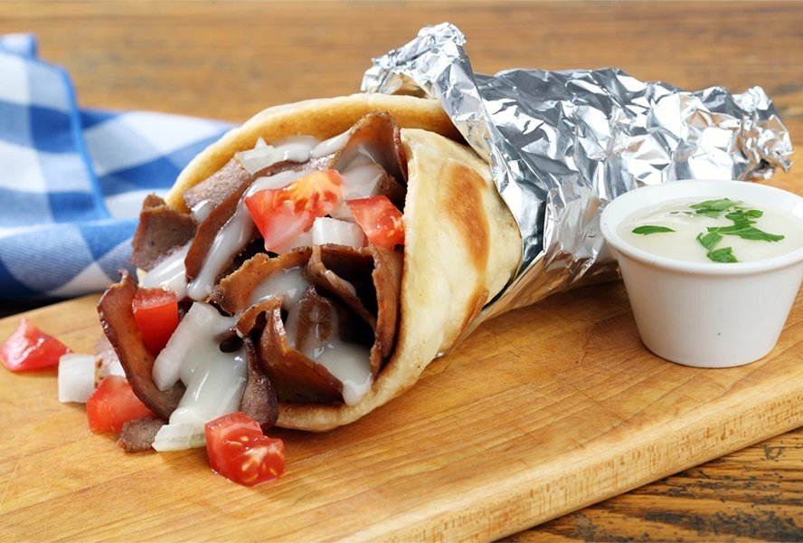 """A photo of a delicious Halifax donair. The Halifax donair was first invented in the 1970s by Peter Gamoulakos. Originally from Greece, he started selling Greek gyros (a pita stuffed with grilled lamb and tzatziki) from his restaurant located off the Bedford Highway. But the sandwich just didn't jive with the East Coast's """"meat and potatoes"""" palate.  Swapping lamb for beef, the brothers whipped up a sweet """"donair sauce"""" and tried again. This time, however, a feeding frenzy erupted and Halifax's signature dish was born. The late-night favourite has become so popular that in 2015, Halifax city council voted to make it the city's official food."""